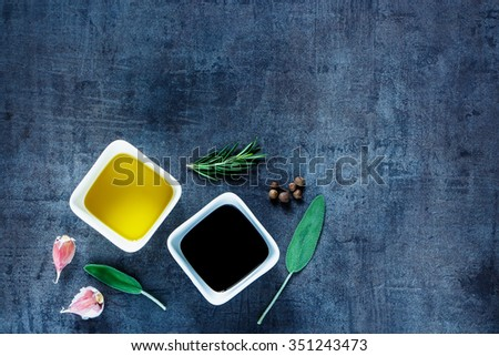 Olive oil and vinegar with peppercorns,  garlic and rosemary on dark vintage background. Top view. Herbs and spices selection. Cooking, Healthy Eating or Vegetarian concept. - stock photo