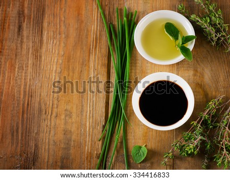 Olive oil, balsamic vinegar and herbs on a vintage wooden background from above. - stock photo