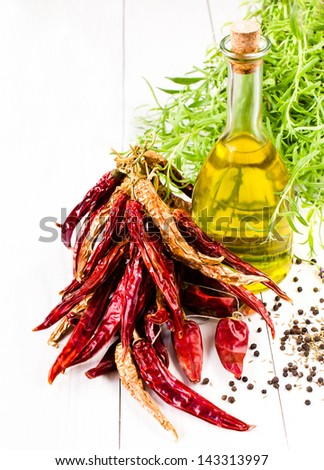 Olive oil bottle, herbs and red vegetables on white background, - stock photo