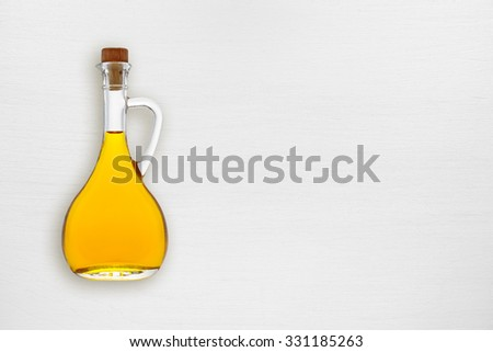 Olive oil bottle on white wooden table top view - stock photo