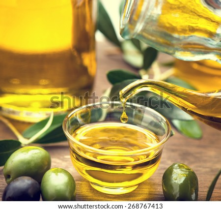 Olive Oil. Bottle pouring Virgin Olive Oil in a bowl close up. Olives and Healthy Olive oil being poured from glass bottle. Diet. Dieting concept. Healthy eating - stock photo