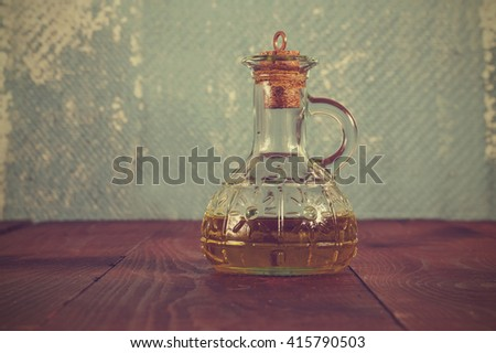 olive oil in a bottle on the background of an old blue wall - stock photo