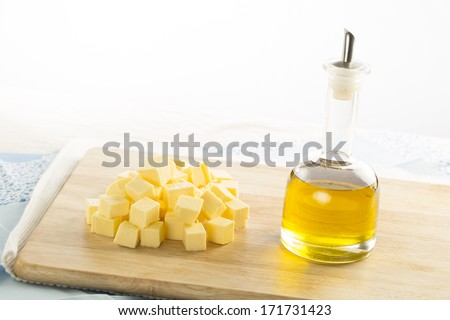 Olive oil in bottle and butter cubes on food preparation surface. - stock photo