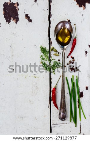 Olive oil in vintage spoon - herbs and spices selection, white wooden background - cooking, healthy eating. Top view. - stock photo