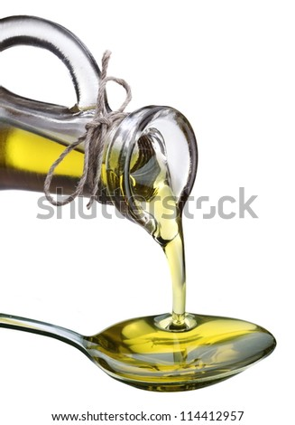 Olive oil is poured from a bottle into a spoon. The image on white background. - stock photo
