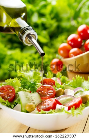 olive oil pouring into bowl of salad - stock photo