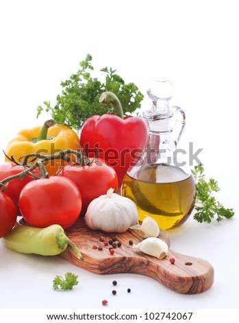 Olive oil, tomatoes, peppers and herbs on a white background - stock photo