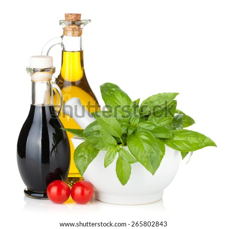 Olive oil, vinegar bottles with basil and tomatoes. Isolated on white background - stock photo