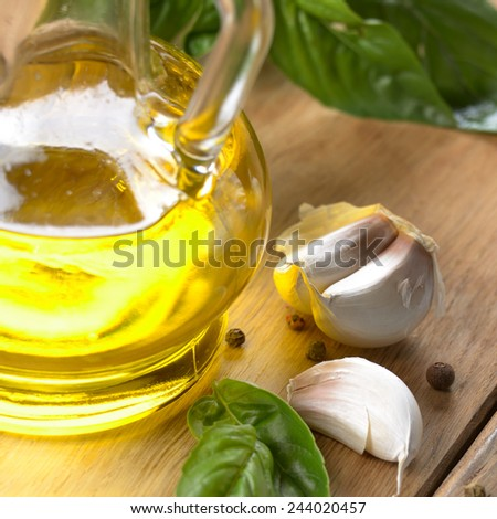 Olive oil with basil leaves and garlic on wooden table - stock photo