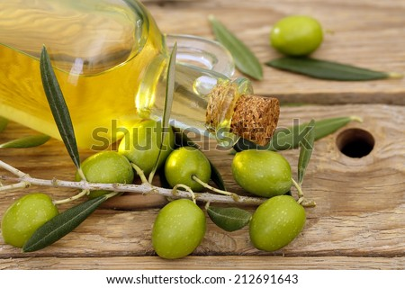 olive oil with branch of olive tree on wooden background - stock photo