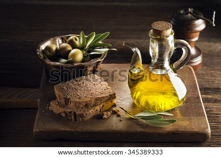 Olive oil with bread on a wooden table. - stock photo