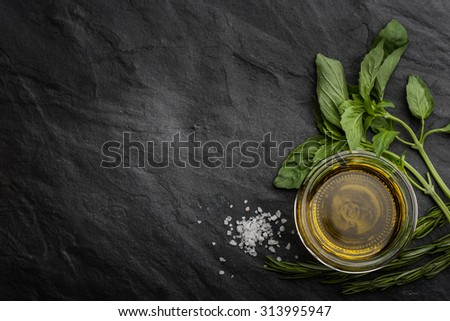 Olive oil  with different greens on the right side of the black stone table - stock photo