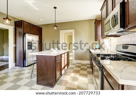Olive tone kitchen room with steel appliances and marble top kitchen island - stock photo