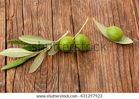 Olives and olive branches and leaves on a wooden floor - stock photo