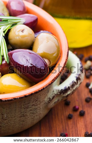 Olives assortiment in green-brown bowl on wooden background with herbs and copy-space - stock photo