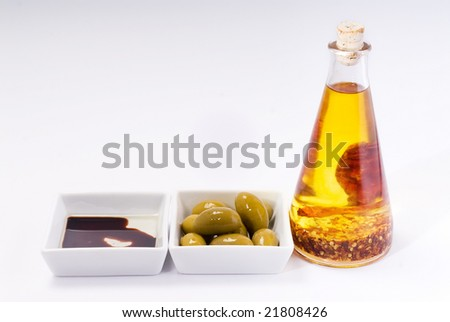 Olives, balsamic vinegar and bottle with chilli infused olive oil. - stock photo