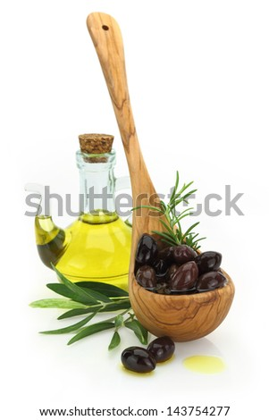 Olives in a wooden spoon and a bottle of virgin olive oil on white background - stock photo