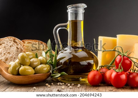 Olives oil,green olive, cheese and cherry tomato on wood - stock photo