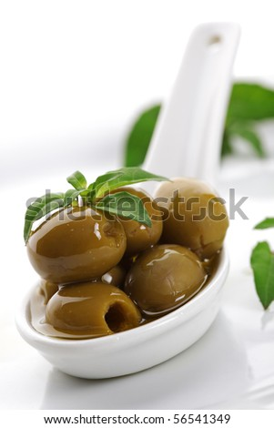 Olives on ceramic spoon with basil and olive oil - stock photo