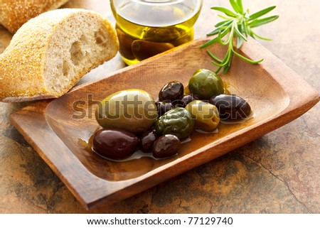 Olives on wooden plate with bread - stock photo