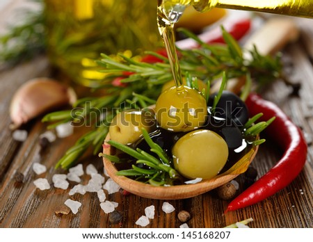 Olives with rosemary and olive oil on a brown table close-up - stock photo