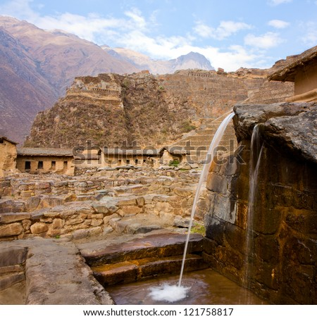 Ollantaytambo - A fountain, part of the Inca domestic water supply, Inca ruins in the background - stock photo