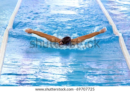 Olympic swimmer during butterfly stroke training in indoor swimming pool. - stock photo