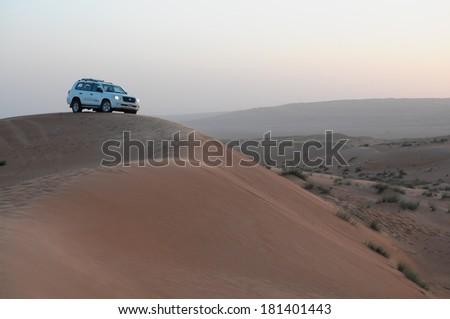 Oman - Dec, 30: White Toyota Land cruiser scaling dunes in the desert on December, 30, 2013. Oman - stock photo