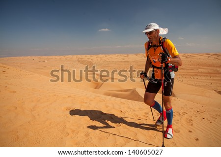 OMAN - DECEMBER 11: Unidentified runner running on dunes on extreme marathon, on December 11, 2011. Raid Oman is one of the most extreme but also one of the most beautiful marathons in the world. - stock photo