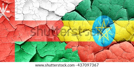 Oman flag with Ethiopia flag on a grunge cracked wall - stock photo