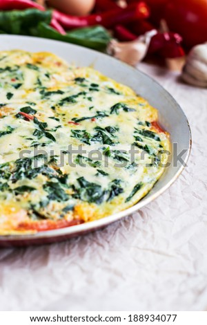 omelet with spinach in a pan placed and vegetables on a table - stock photo