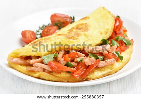 Omelette with ham and vegetables on white plate, close up view - stock photo