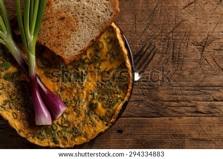 Omelette with toast and onions on rustic wooden table - stock photo