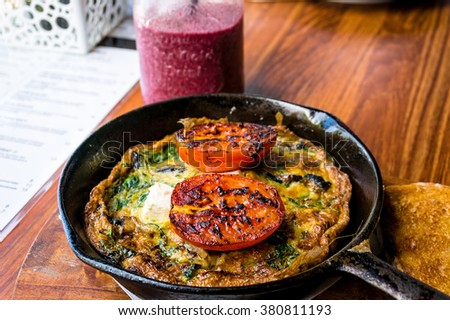 Omelette with tomato and greens on cast iron frying pan. Rustic breakfast omelette with grilled tomato and herbs and berry smoothie. Selective focus, shallow dof - stock photo
