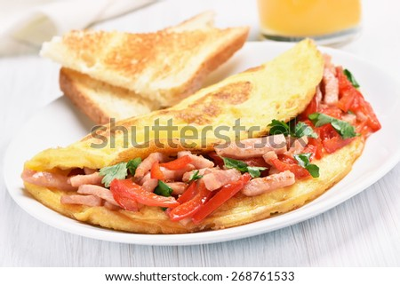 Omelette with vegetables and ham on white wooden table - stock photo