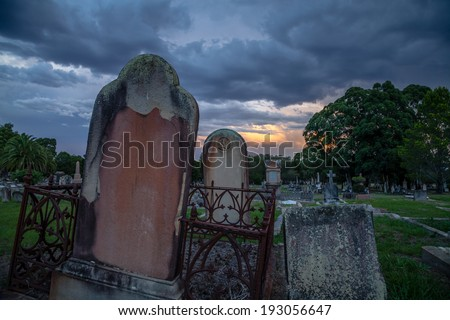 Ominous storm clouds and sunset light over very old public cemetery with leaning sandstone tombstones, rusted iron railings and lush grass and trees - stock photo