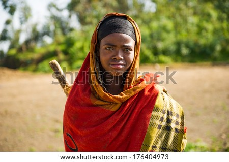 OMO, ETHIOPIA - SEPTEMBER 22, 2011: Unidentified Ethiopian wearing the orange traditional clothes. People in Ethiopia suffer of poverty due to the unstable situation - stock photo