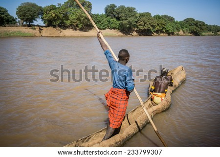 OMO VALLEY, ETHIOPIA - DECEMBER 28, 2008: Men of the ethnic Hamer-Banna group cross the Omo River near Turmi using a wooden boat on December 28, 2008 in Omo Valley, Ethiopia. - stock photo