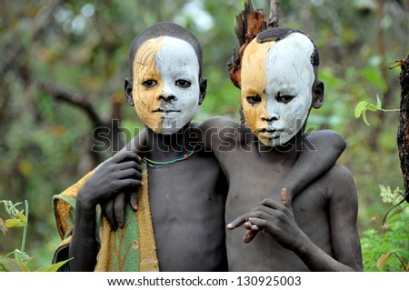 OMO VALLEY, ETHIOPIA - FEB 5: unidentified Surma posing by the river and painting themselves,. Surma in the Omo valley,could disappear because of Gibe III hydroelectric dam on Feb 5, 2013 in Omo Valley, Ethiopia. - stock photo
