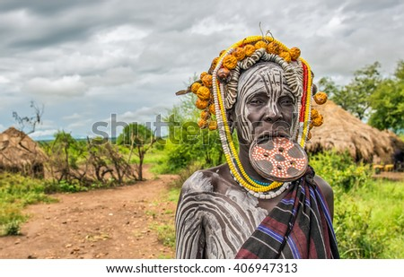 OMO VALLEY, ETHIOPIA - MAY 7, 2015 : Woman from the african tribe Mursi with a big lip plate in her village. - stock photo