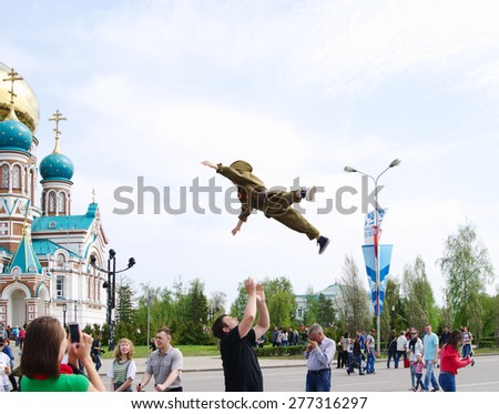 OMSK, RUSSIA -  MAY, 9, 2015: Celebration of 70th anniversary of Victory. Happy father tossed high into air little boy in soldier's uniform.  - stock photo