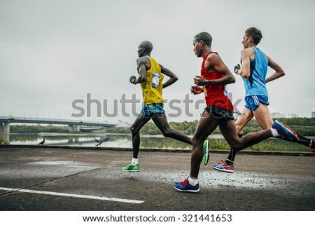 Omsk, Russia -  September 20, 2015: three leaders of the marathon running along the embankment of the Irtysh river during Siberian international marathon - stock photo