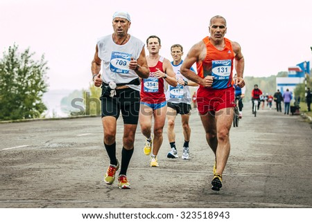 Omsk, Russia -  September 20, 2015: two elderly runners run ahead of a large group of runners during Siberian international marathon - stock photo