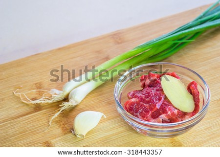 On a bamboo cutting board are spring onions, a piece of garlic, and a glass bow filled with fresh beef slices and one piece of ginger. - stock photo