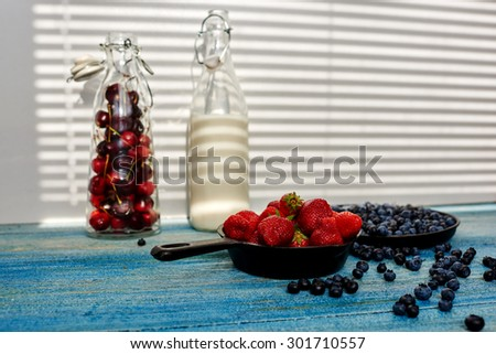 On a blue vintage wooden desk are two cast iron pans that sprinkling strawberries and blueberries near the scene along there are two glass bottles with milk and cherries - stock photo