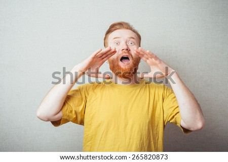 on a gray background man with a beard in a yellow T-shirt calling someone - stock photo