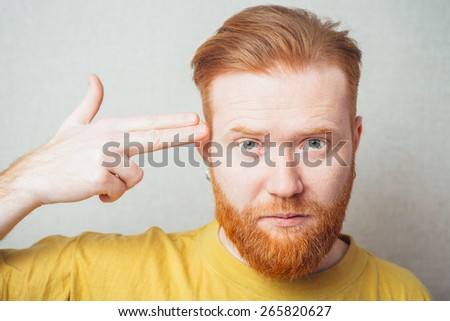 on a gray background man with a beard in a yellow T-shirt put up a gun - stock photo