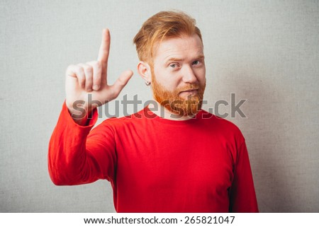 on a gray background man with a beard in the red shirt showed his index finger up - stock photo
