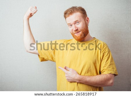 on a gray background man with a beard in the yellow shirt is outraged and shows forefingers biceps - stock photo