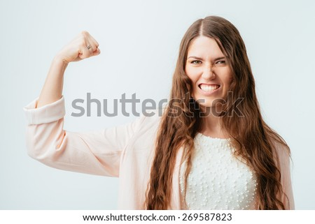 on a gray background young girl shows biceps - stock photo